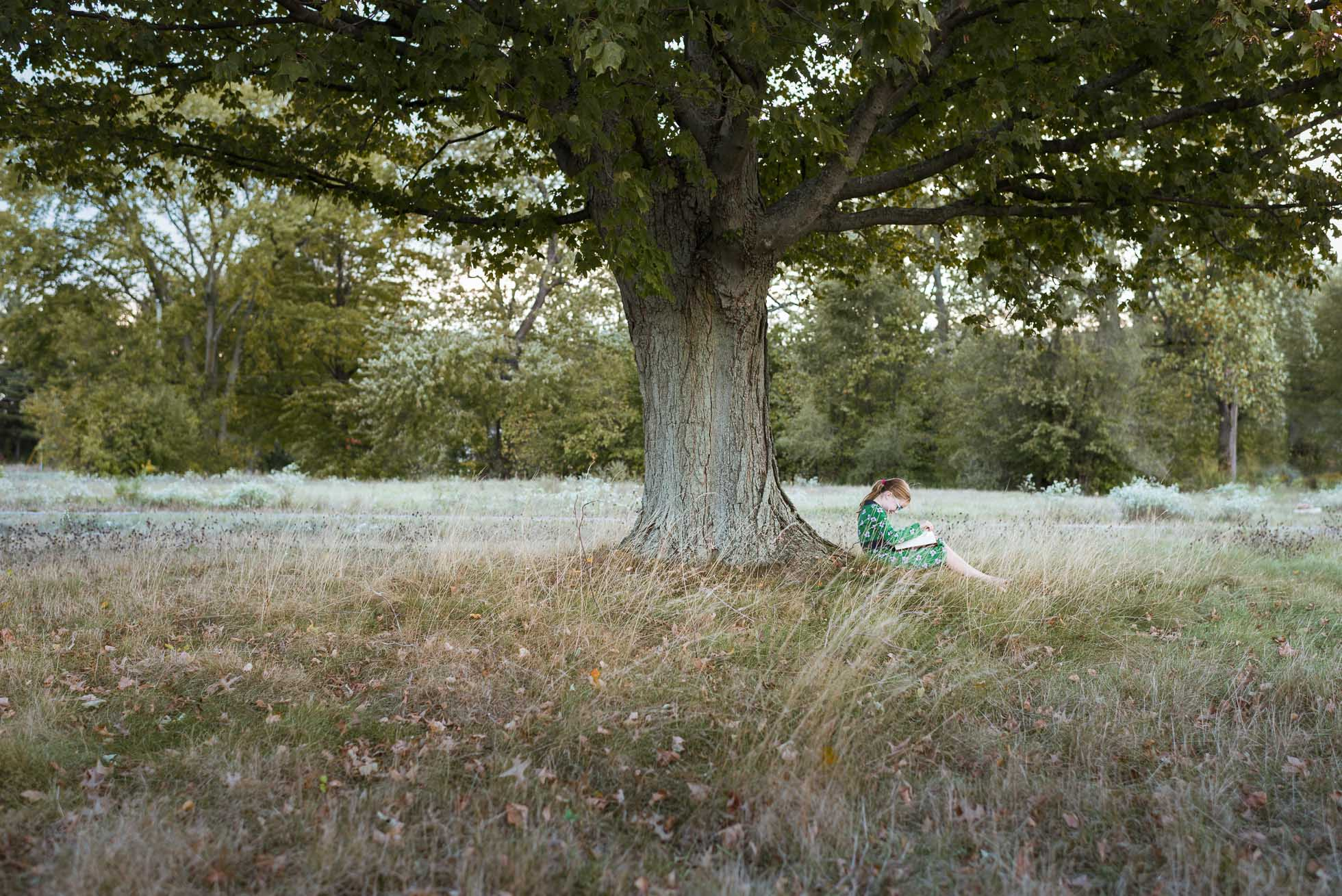 A little girl reads a favorite book while sitting beneath a tree, wearing a green dress.