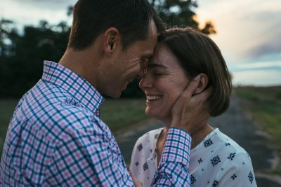 A husband pulls his wife in close as they share a smile and a kiss during a photo session at golden hour.