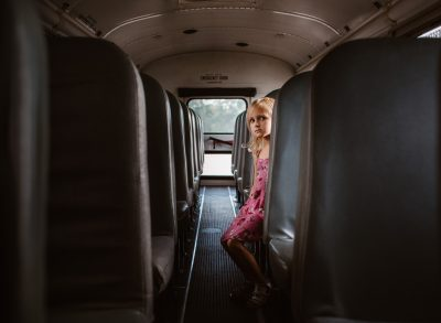 first bus ride young girl in pink dress school bus edmond ok photographer kate luber photography oklahoma city natural light