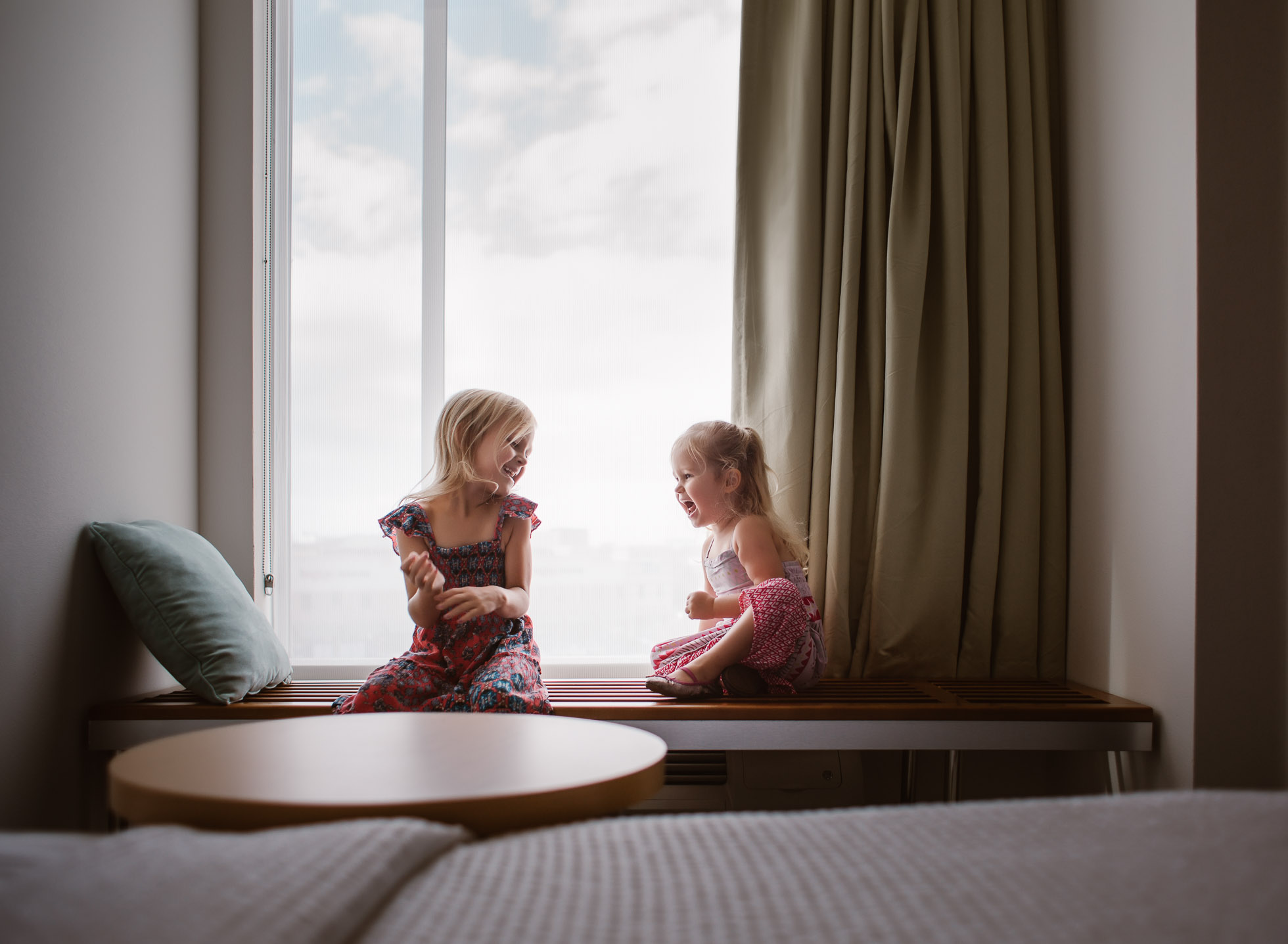sister laughs young girls sitting in window hotel edmond ok photographer oklahoma city natural light photographer kate luber photography