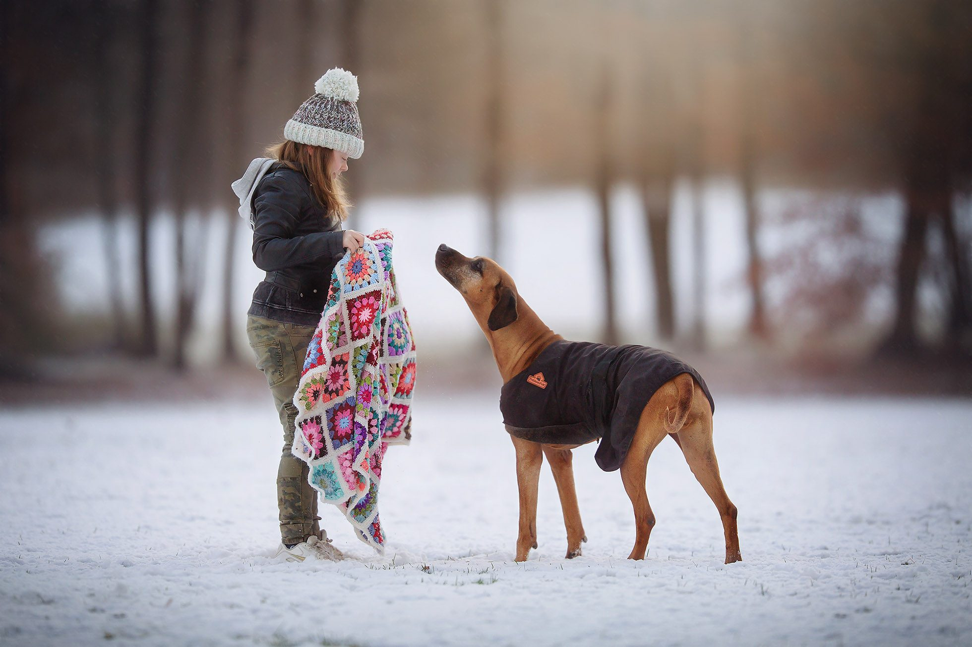Color Canon portrait of a girl with a hat and a brown dog in playing in the snow by Willie Kers