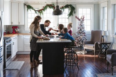 A family of five gathers around the kitchen island while Mom rolls out cookie dough. The season is Christmas and the kitchen is decorated with garland and a tree. The scene is set in a Michigan farmhouse.