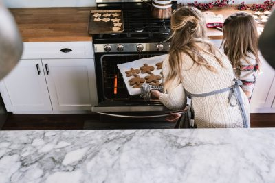 A mother and her daughter removed gingerbread cookies from the warmth of the oven while sugar cookies sit on top.