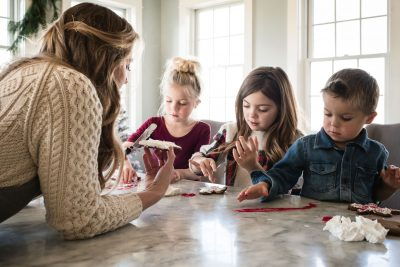 A mother relives memories and tells stories to her children at their kitchen island as they all frost and decorate gingerbreak cookies for Christmas.