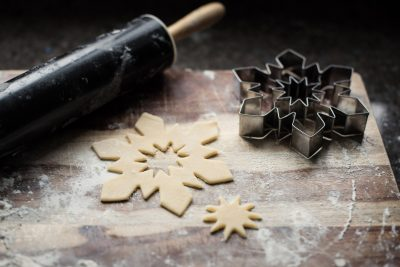 A rolling pin, snowflake cookie cutter, and cookie parts are displayed on a wooden cutting board covered in flour on a dark background. The cookie was cut while wishing for a white Christmas on Christmas Eve.