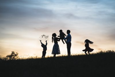 A silhouette of a family of five. Father hands the youngest child to Mother, while older brother throws weeds in the air and Sister dances and twirls on a hilltop. All defy gravity and soar, if only for a moment.