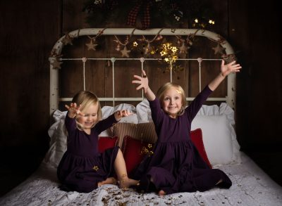 and bright sisters on bed christmas confetti edmond ok photographer oklahoma city studio light photographer kate luber photography