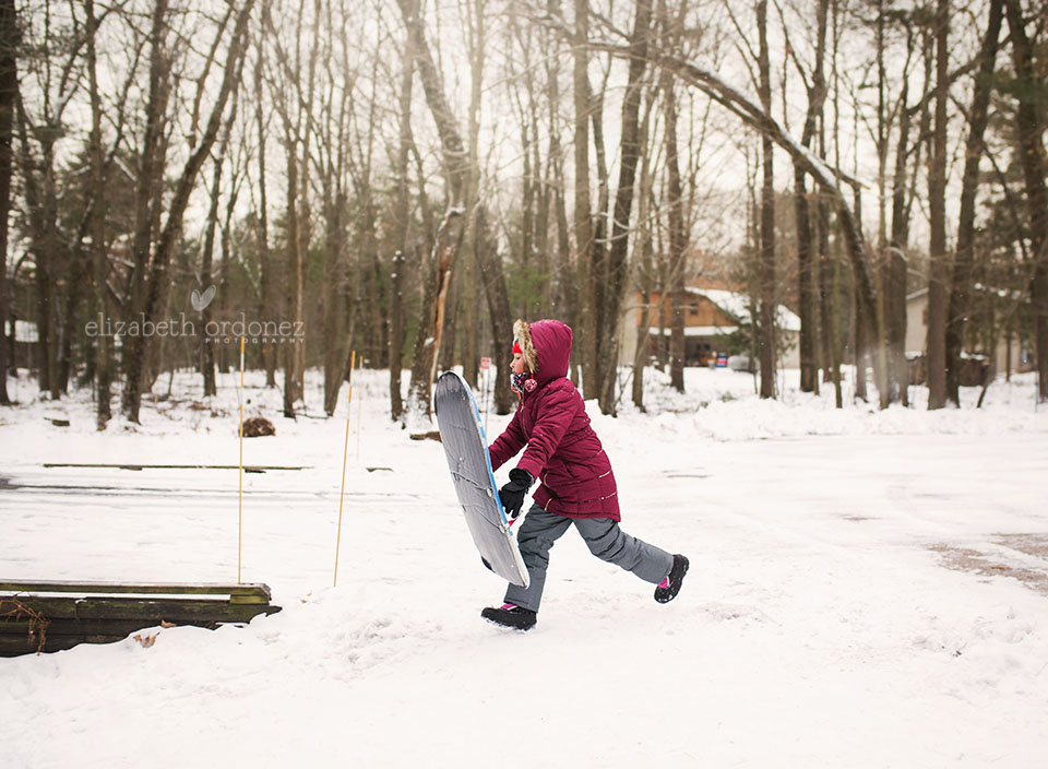 girl running with a sled in a front yard