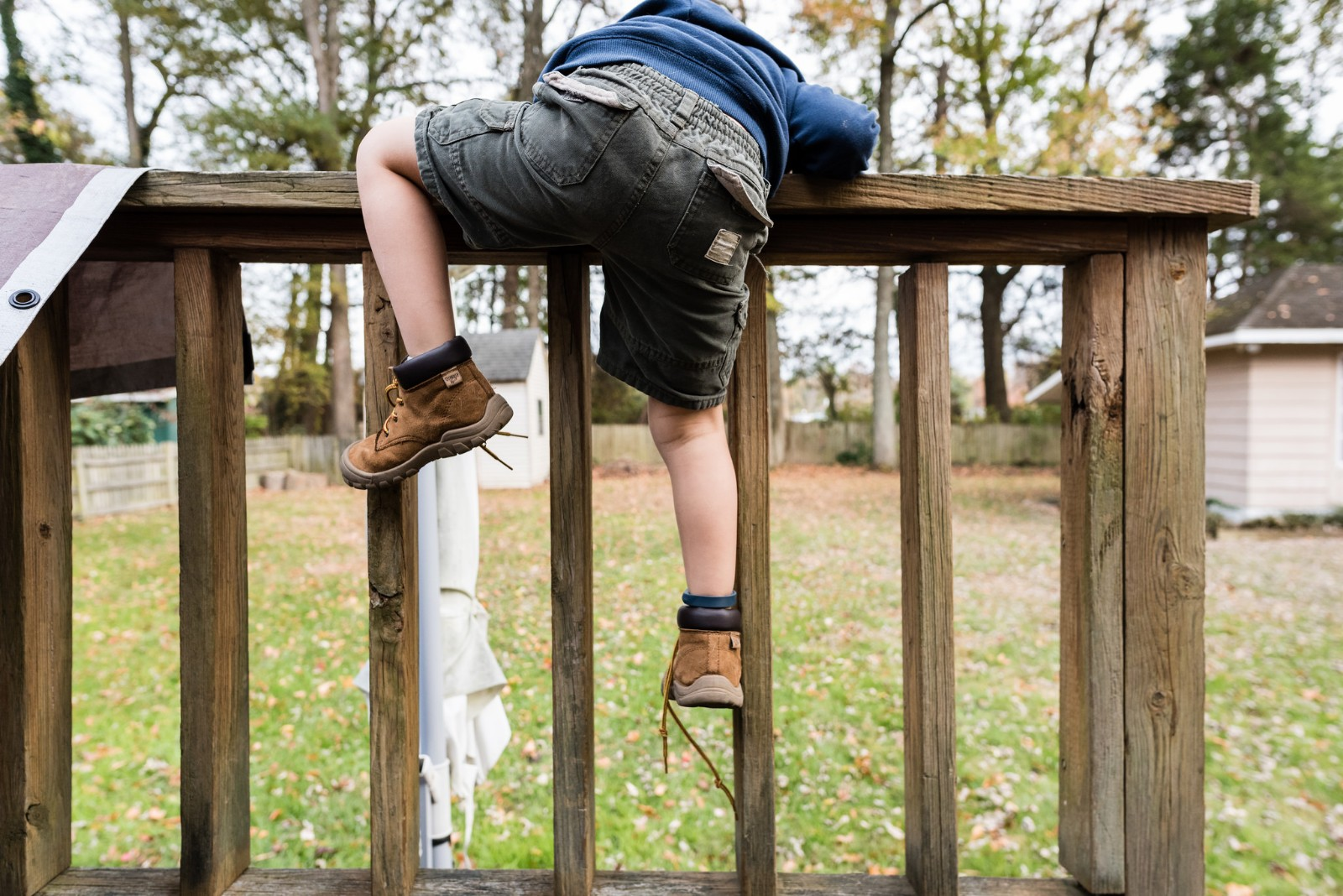 Child crawling over fence