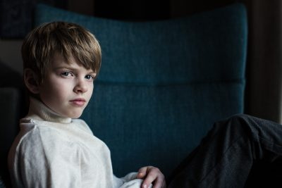 A boy sits sideways in a chair at a Hilton Hotel near the Magnificent Mile in Chicago wearing his new Zara turtleneck. His style is reminiscent of his uncle's.