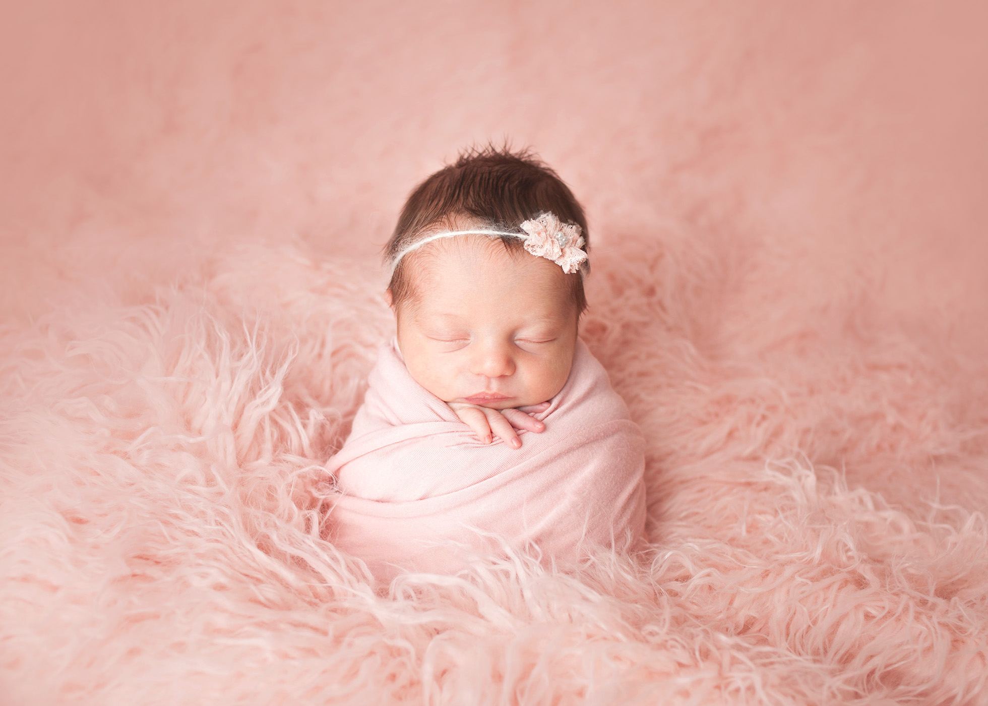 Studio newborn session of girl in potato sack pose on pink flokati by Cleveland newborn photographer Chelsey Hill Photography