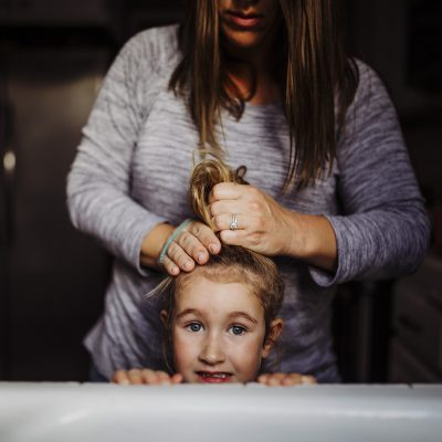 francesca marchese photography self portrait mother and daughter doing hair top knot orange county long beach family photographer