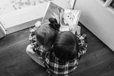 older boy reading book aloud to little girl