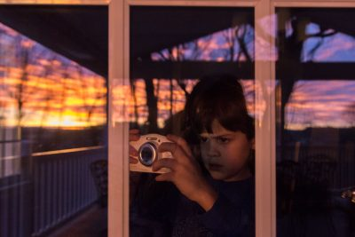 boy taking picture of sunrise through glass