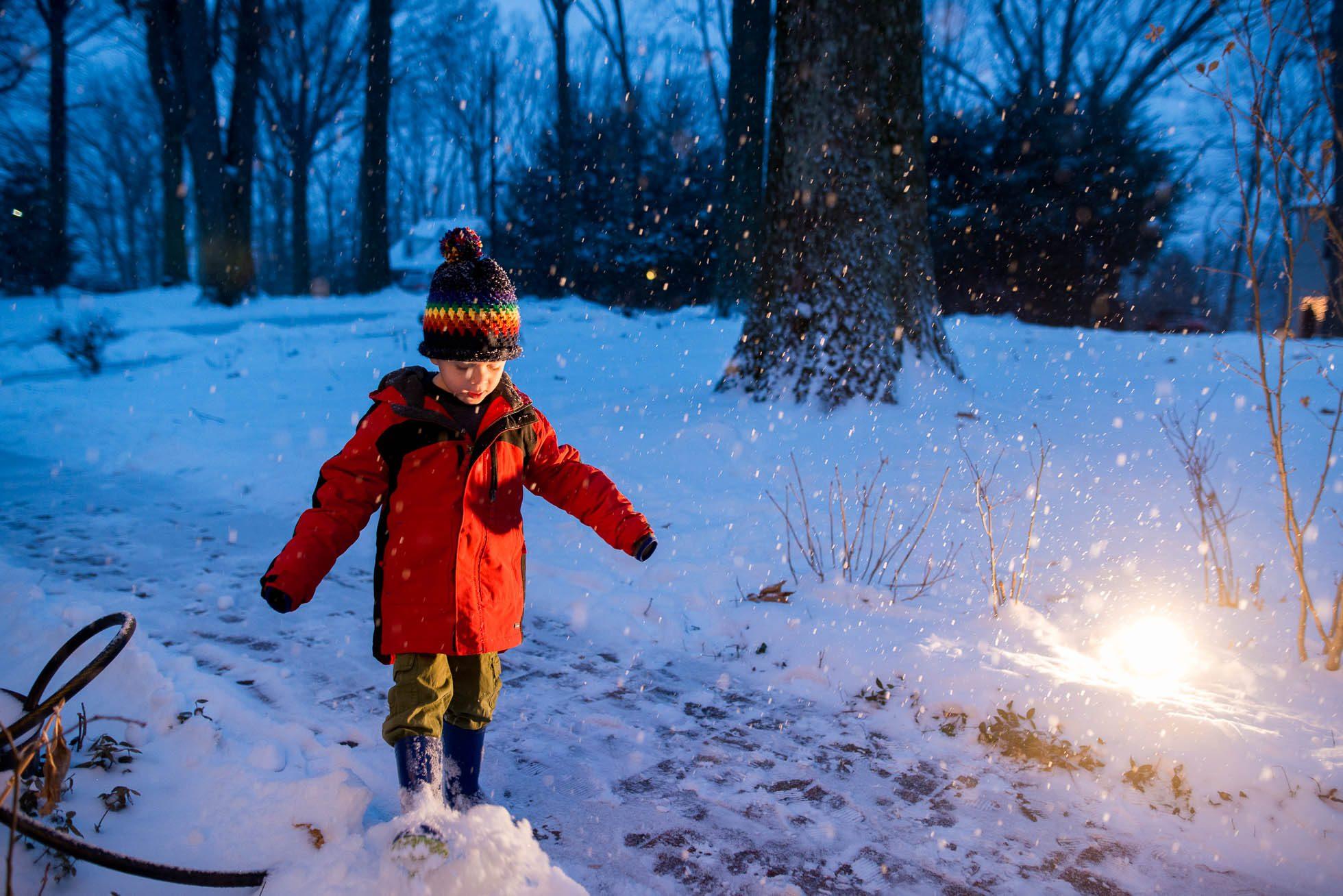 boy walking in falling snow in the evening