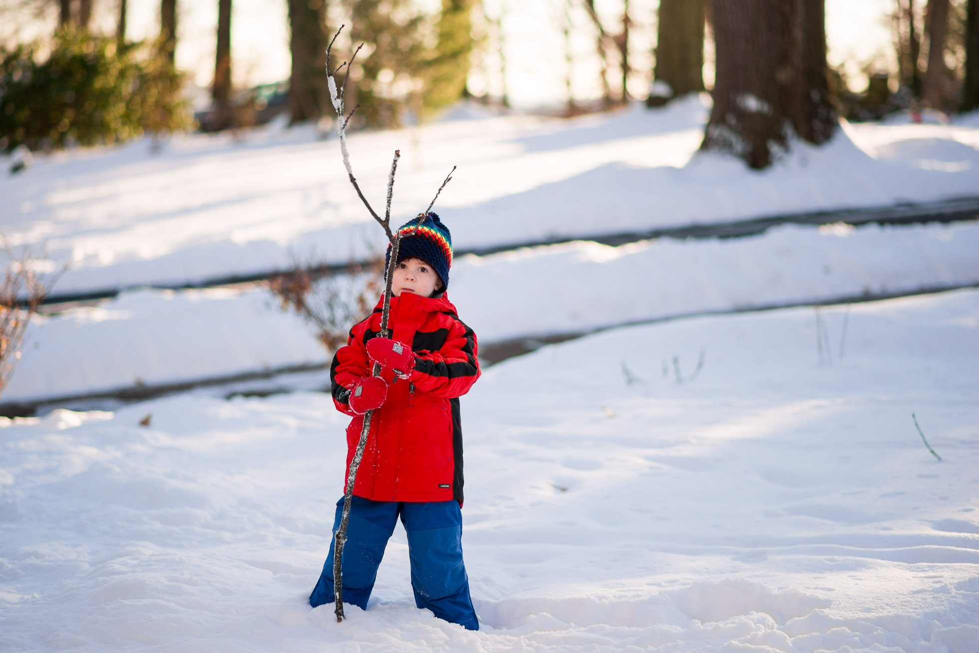 boy standing in snow with big stick