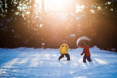 brothers playing and throwing snow