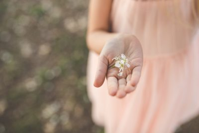 girl holding spring flowers in hand by tiffany kelly
