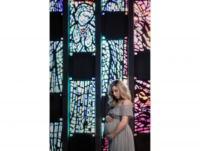 """""""Eyes of Faith"""" look down upon a pregnant woman as she ponders and gives thanks for her baby while standing in front of stained glass windows in a chapel."""