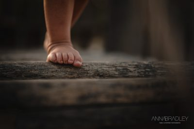 Little boy toes holding on photograph by Anna Bradley