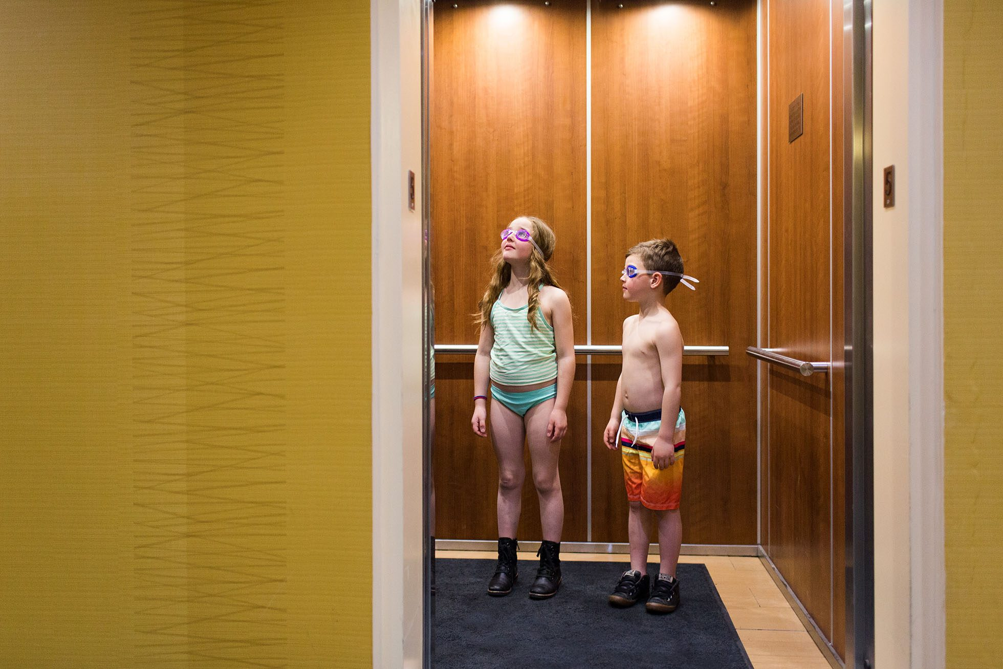 Photo of 2 kids on an elevator on their way to the hotel pool, wearing just bathing suits, goggles and boots.