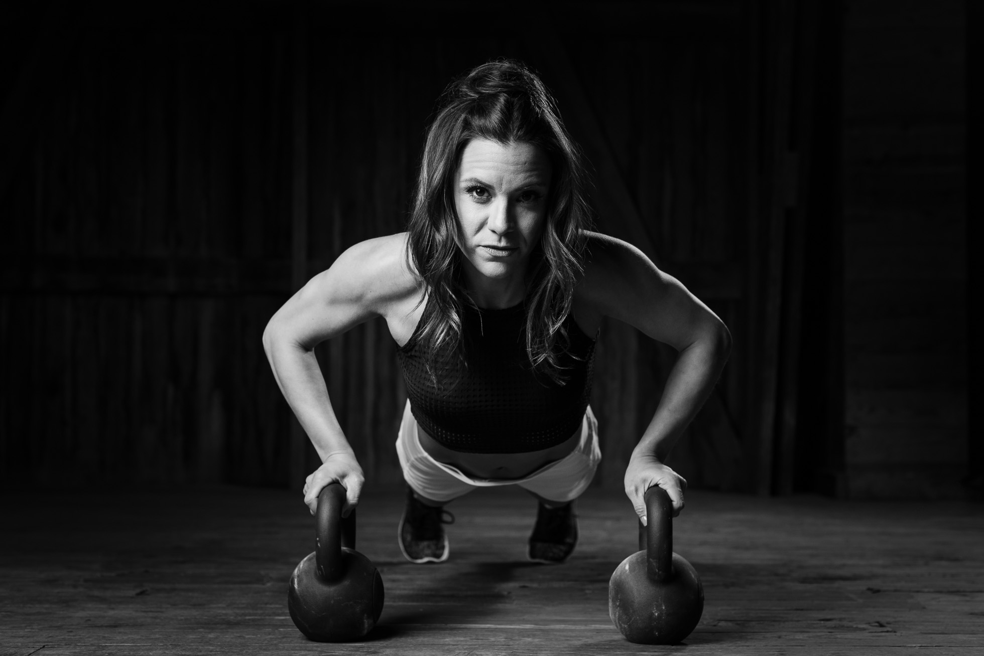 A fitness instructor and personal trainer does a pushup on a kettlebell while making eye contact with the viewer.