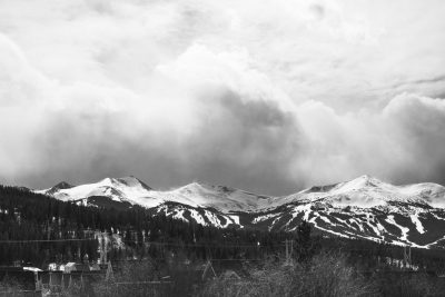 A view of Breckenridge ski slopes from a hilltop on the outskirts of town, taken as clouds are rolling in over the mountain peaks.
