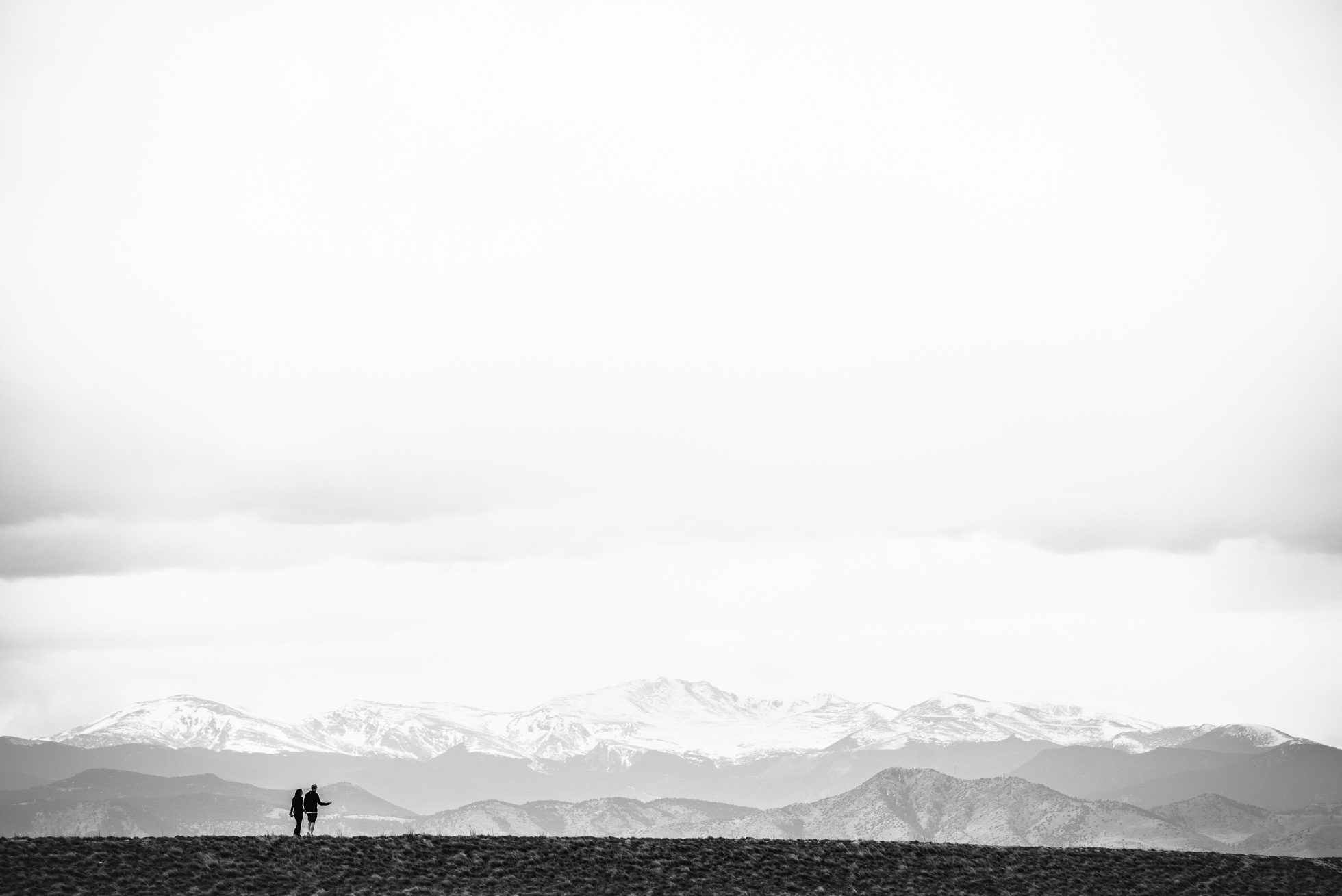 A couple walks on a ridge in Lowry, Colorado, in the shadow of the Rocky Mountains which are off in the distance.