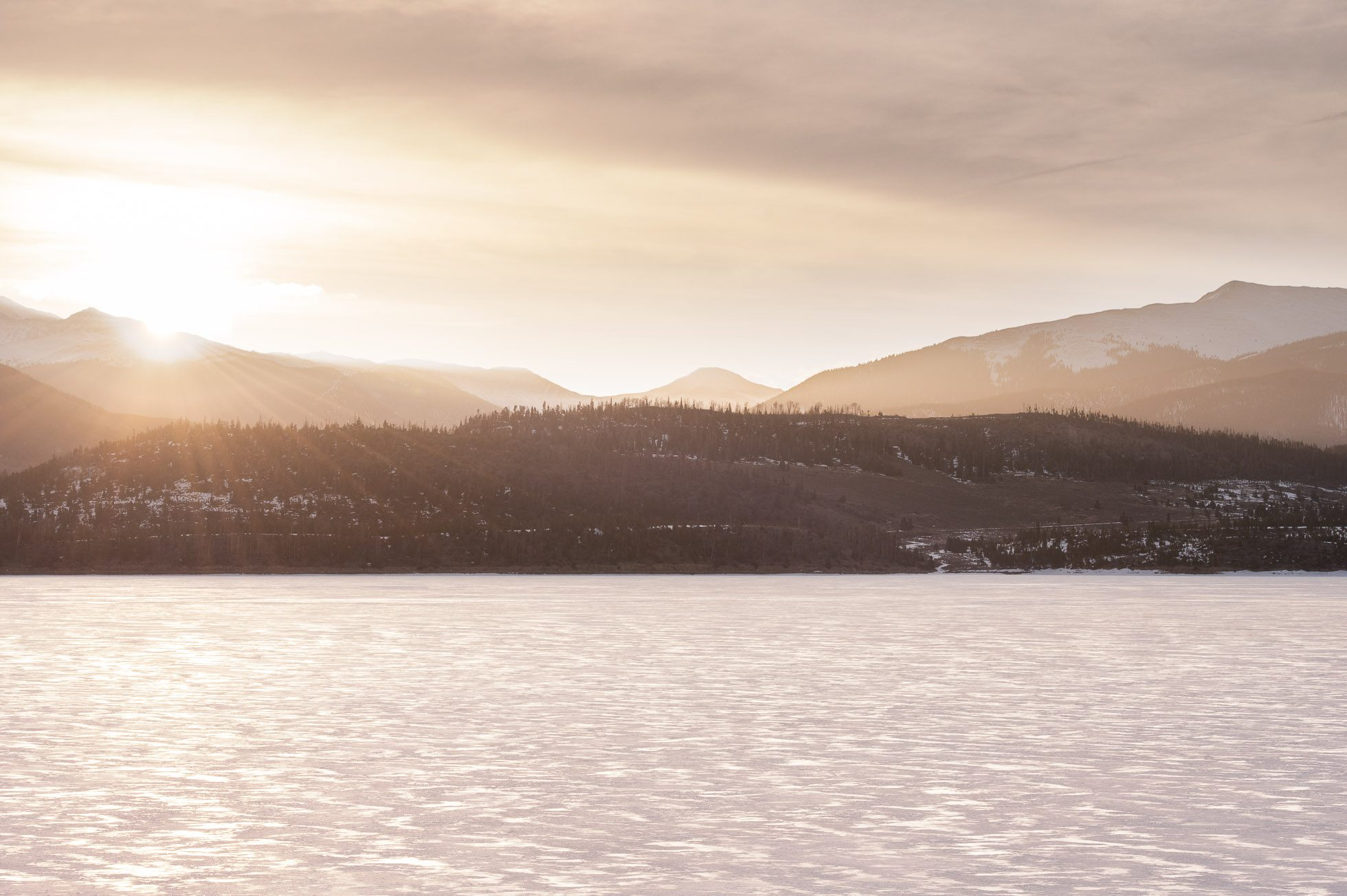 A photograph looking over Dillon Reservoir in Frisco, CO at the mountains in the distance as the sun rises