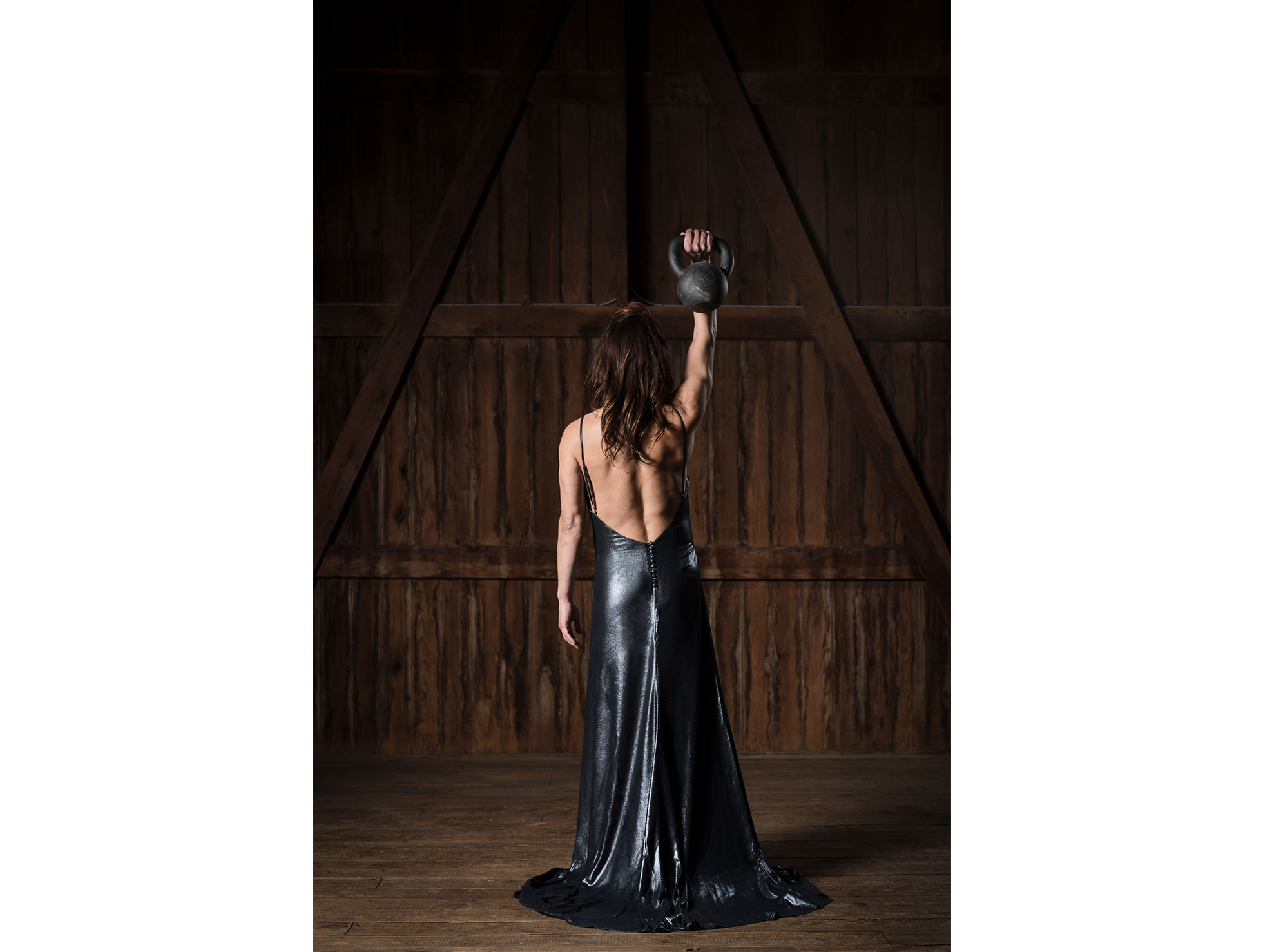A woman in a feminine evening gown fiercely holds a kettlebell over her head, displaying physical strength and toughness as a female.