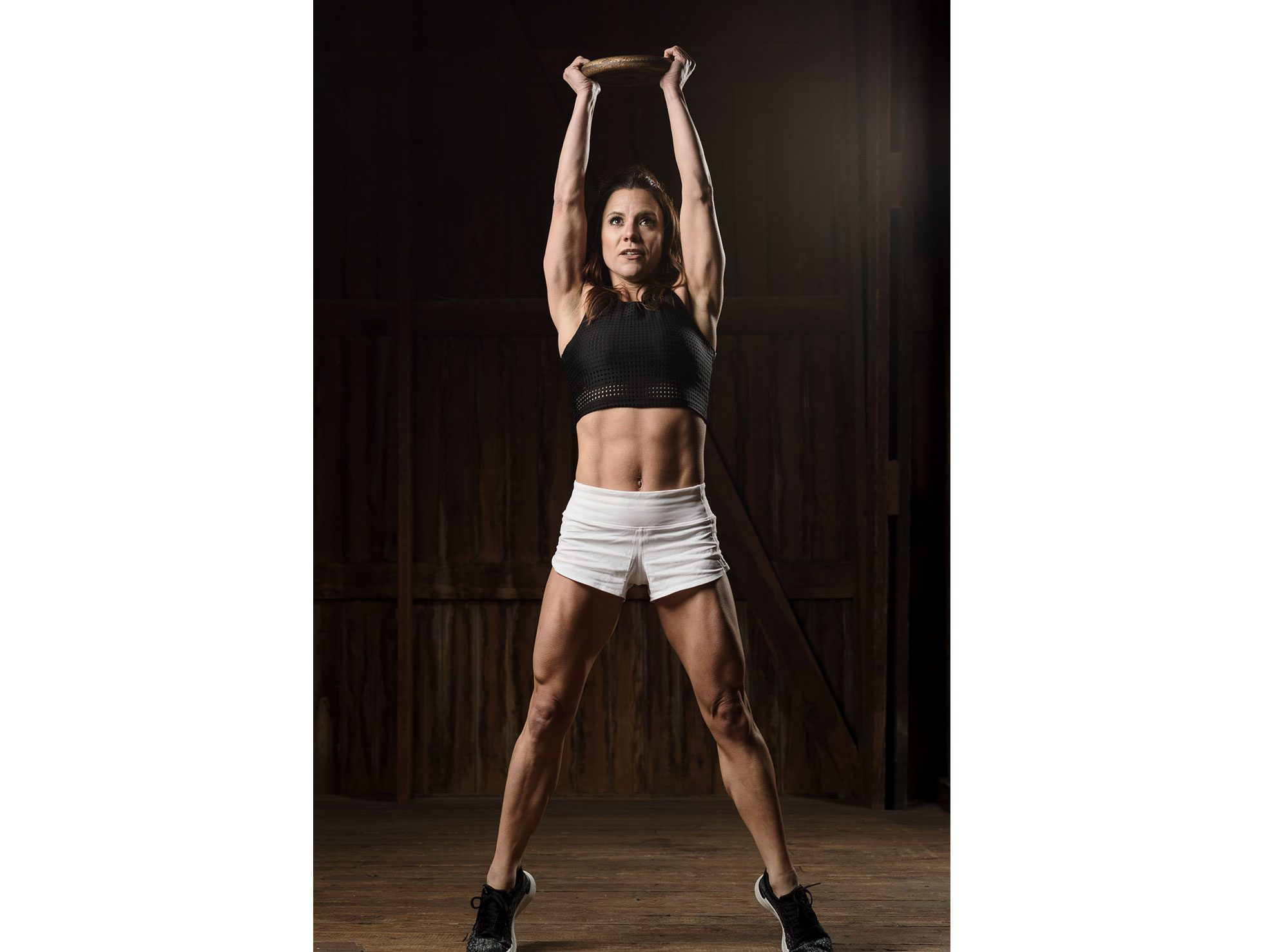 A personal trainer lifts a weighted plate into the air as she comes up on her toes, flexing multiple muscle groups as she does so.