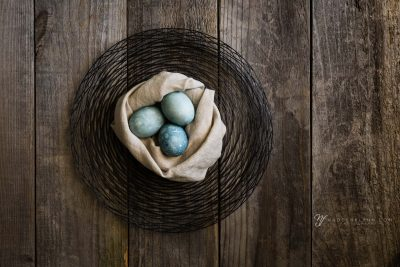 three blue eggs nestled in a linen cloth on wire and wood background
