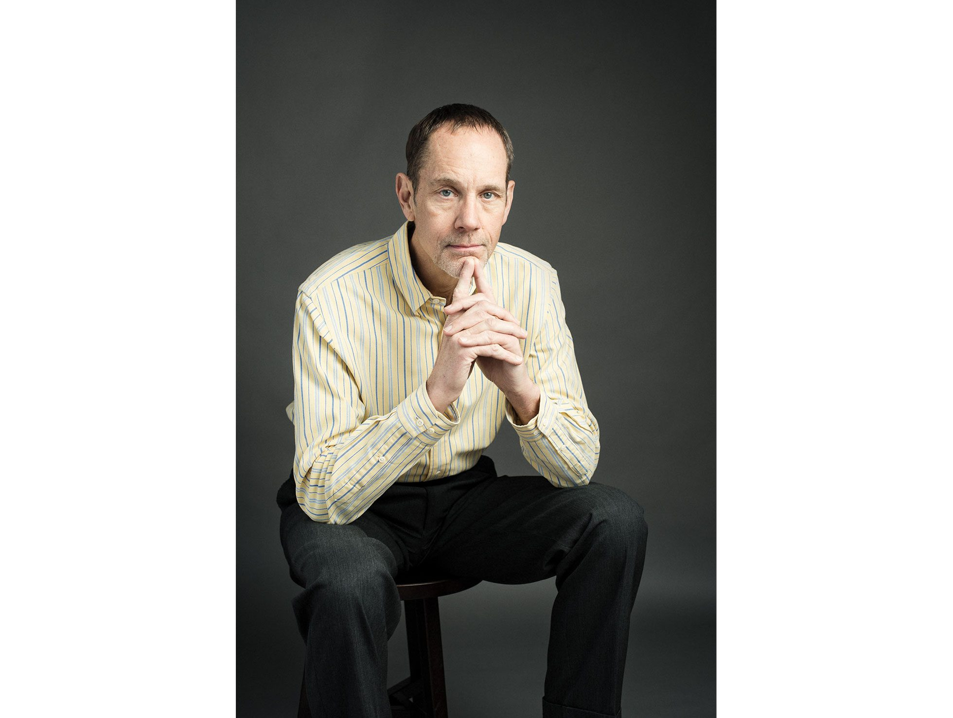 A portrait of Tim Ryan of Ryan Career Consulting, an entrepreneur. He sits on a stool and appears to be deep in thought with his steepled fingers near his lips.Personal branding and headshot session sample.