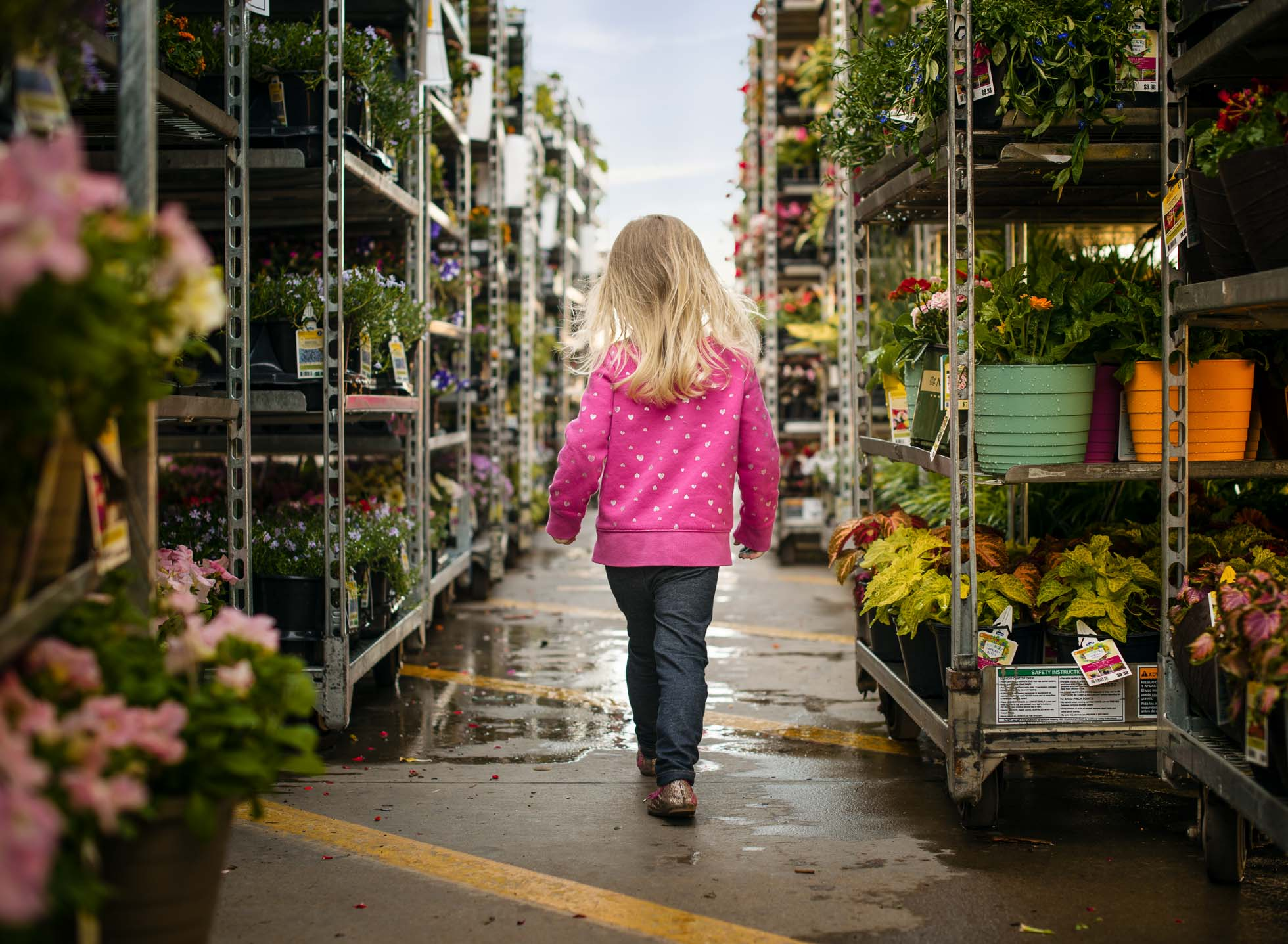 girl in pink walking down rows in garden center its beginning to look a lot like spring girl pink edmond ok photographer oklahoma city natural light photographer kate luber photography