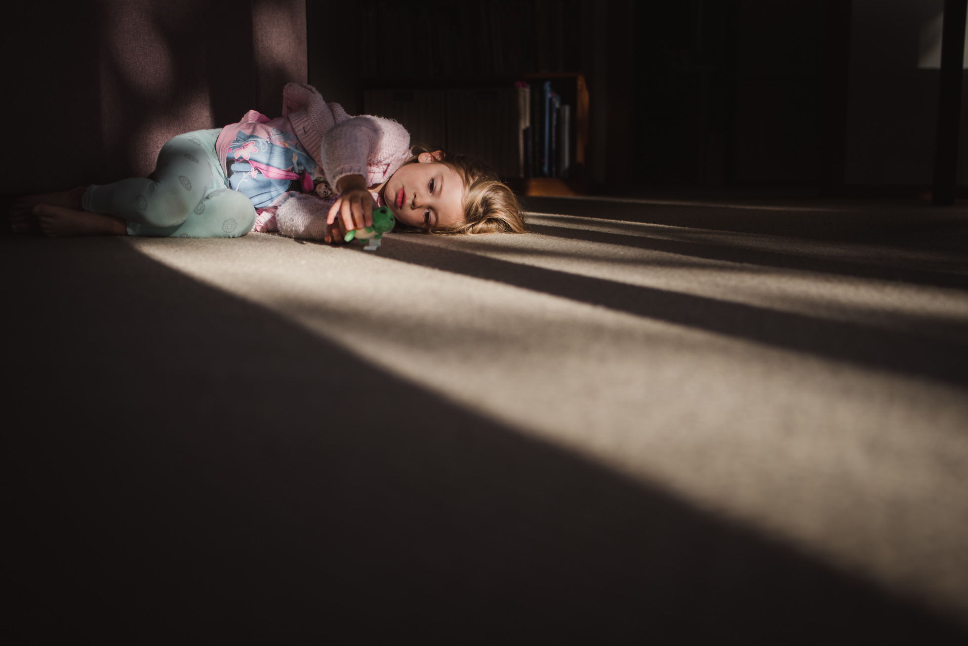 girl lying in a patch of light by Aimee Glucina