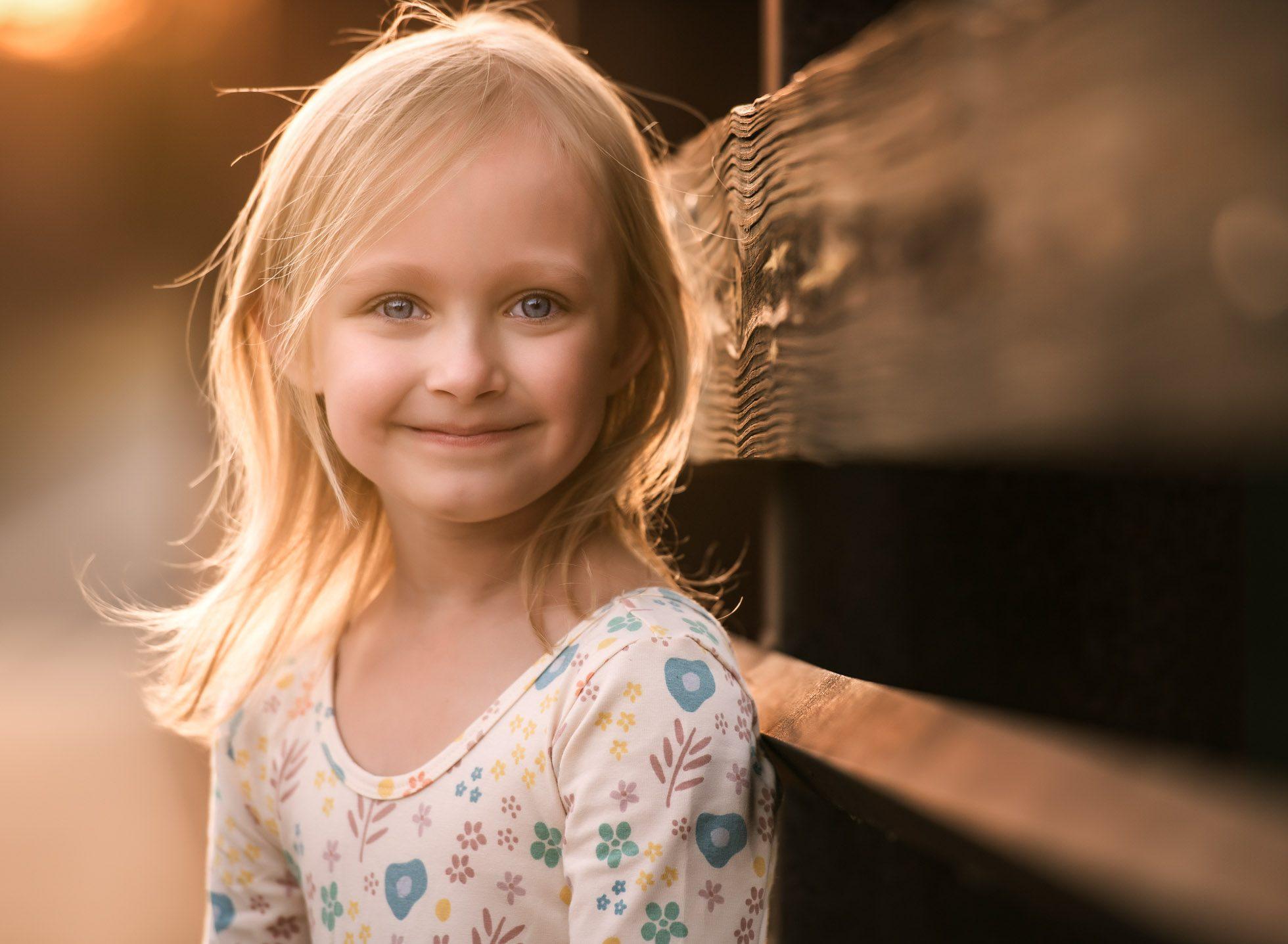 Young blonde girl on bridge in floral dress the sweetest smile girl on bridge edmond ok photographer oklahoma city natural light photographer kate luber photography