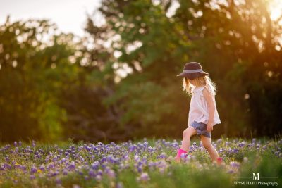 young girl with a hat walking in a field of bluebonnets