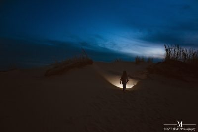 a small girl walks on the sand dunes at night with a flashlight