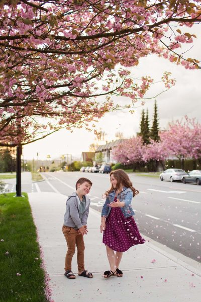 Happy siblings playing under the cherry trees before bedtime.