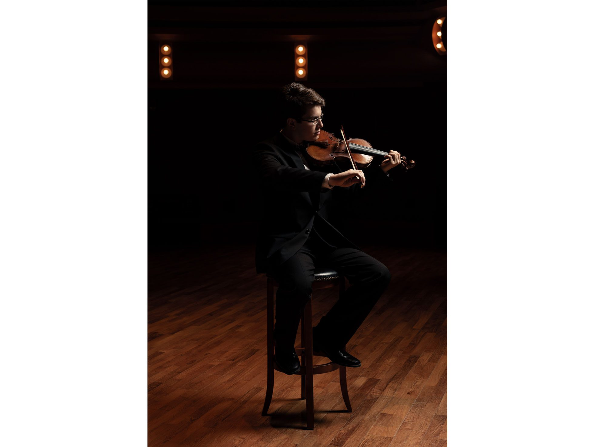 Portrait of a senior high school violinist playing his violin on the stage of the Leighton Concert Hall in the Darbartolo Performing Arts Center at Notre Dame University in South Bend, Indiana.