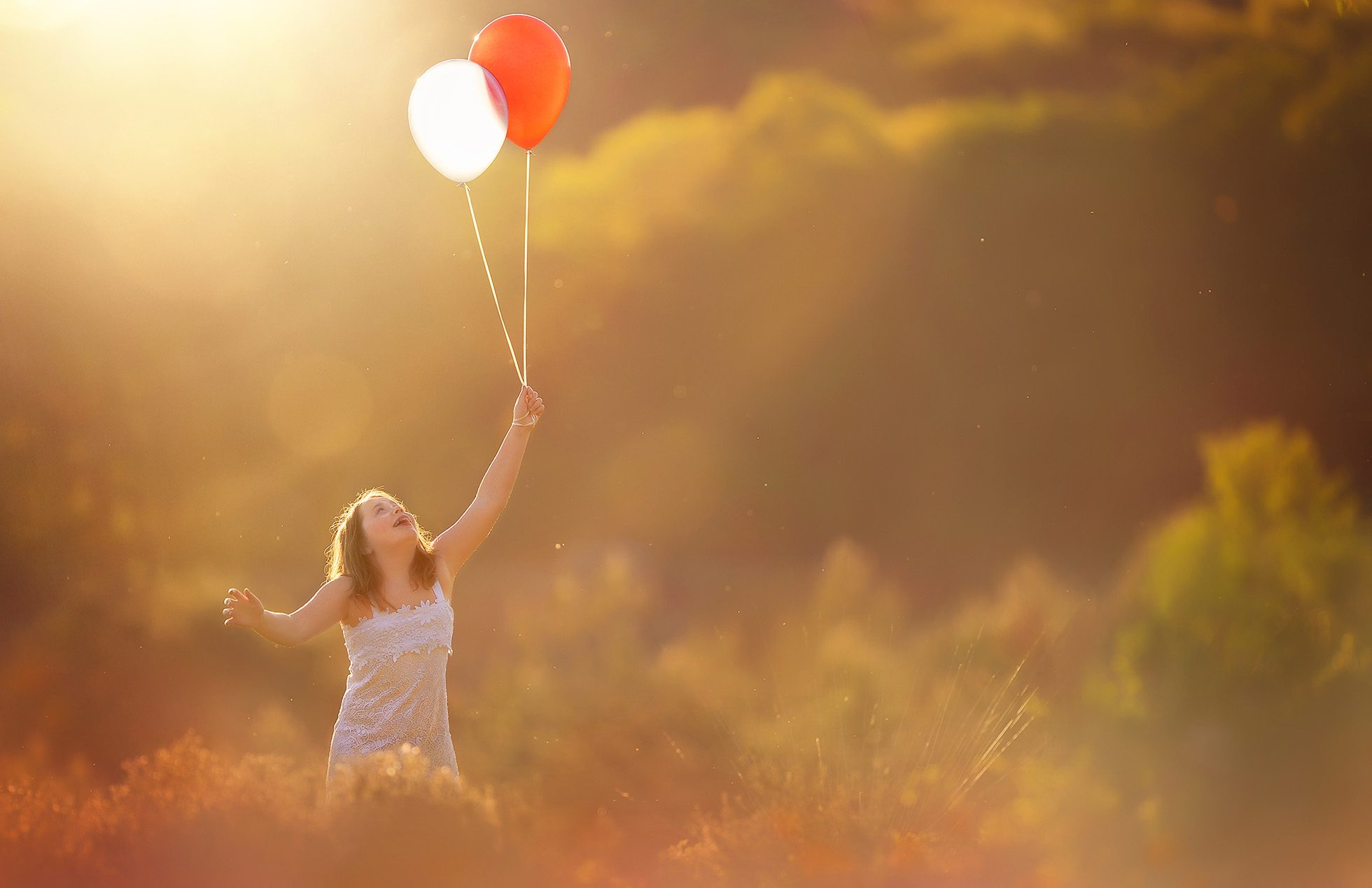 Click pro Canon color sunset portrait running with big red and white balloons through a field of gold by Willie Kers