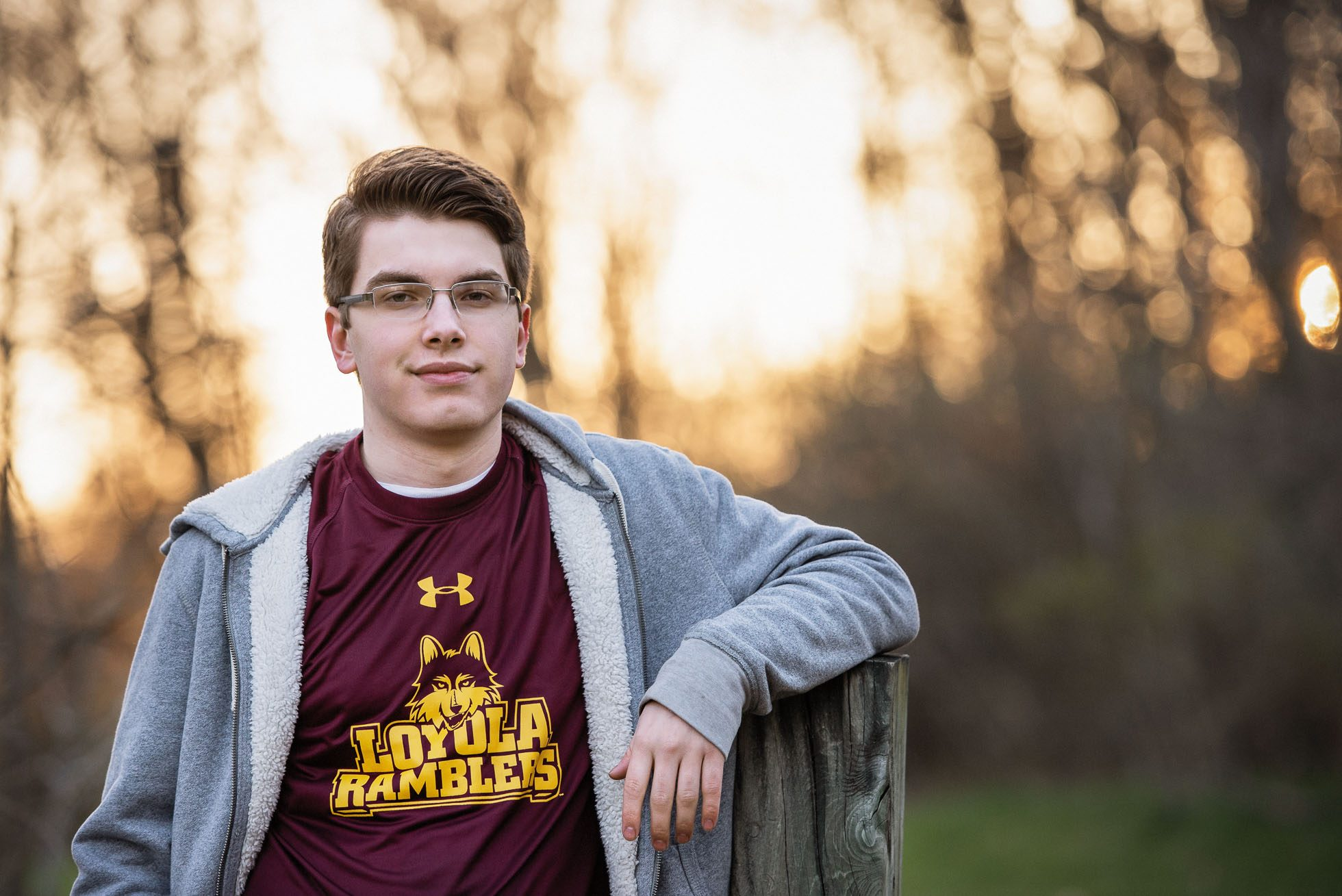 A senior boy of the class of 2018 stands leaning with his elbow on a post and wearing a Loyola Ramblers Underarmour t-shirt while smirking at the camera.