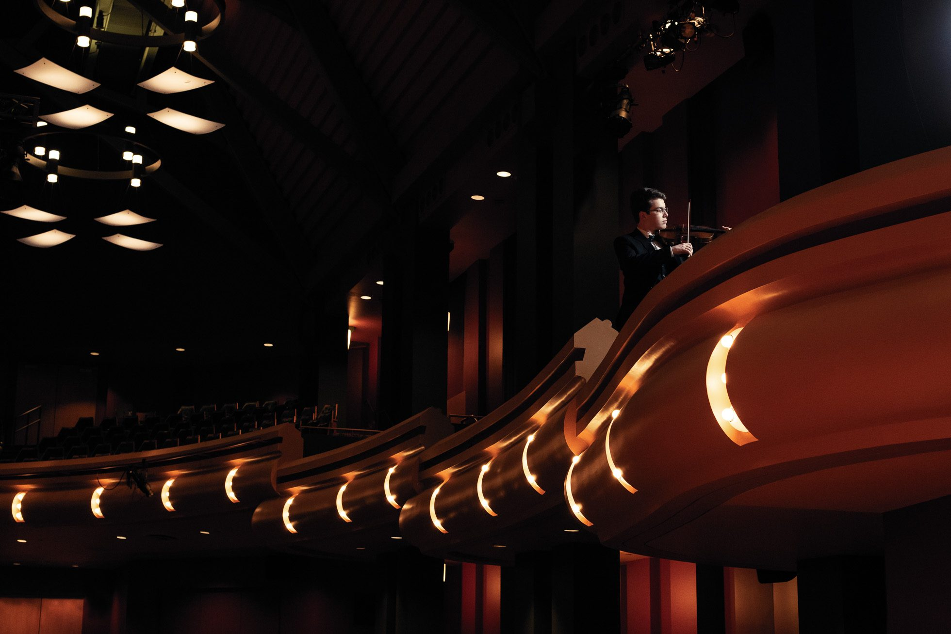 A high school senior boy plays his violin in the balcony of the Leighton Concert Hall of Notre Dame University's Debartolo Performing Arts Center.