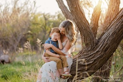 mother sitting on a tree holding her son who is covering his eyes
