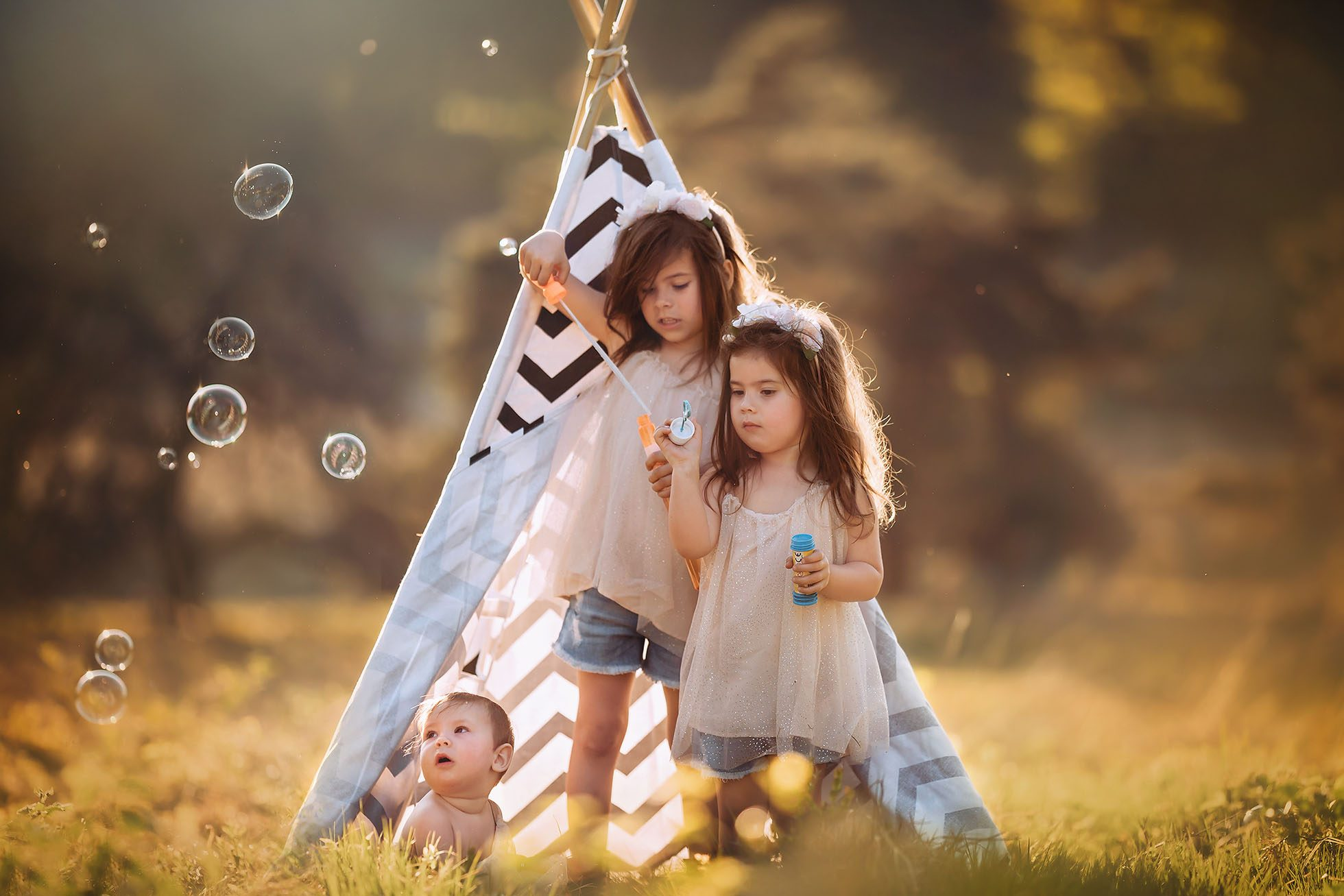 Sony fine art color portrait of three little girls blowing bubbles in front of a tipi in the forest by Willie Kers