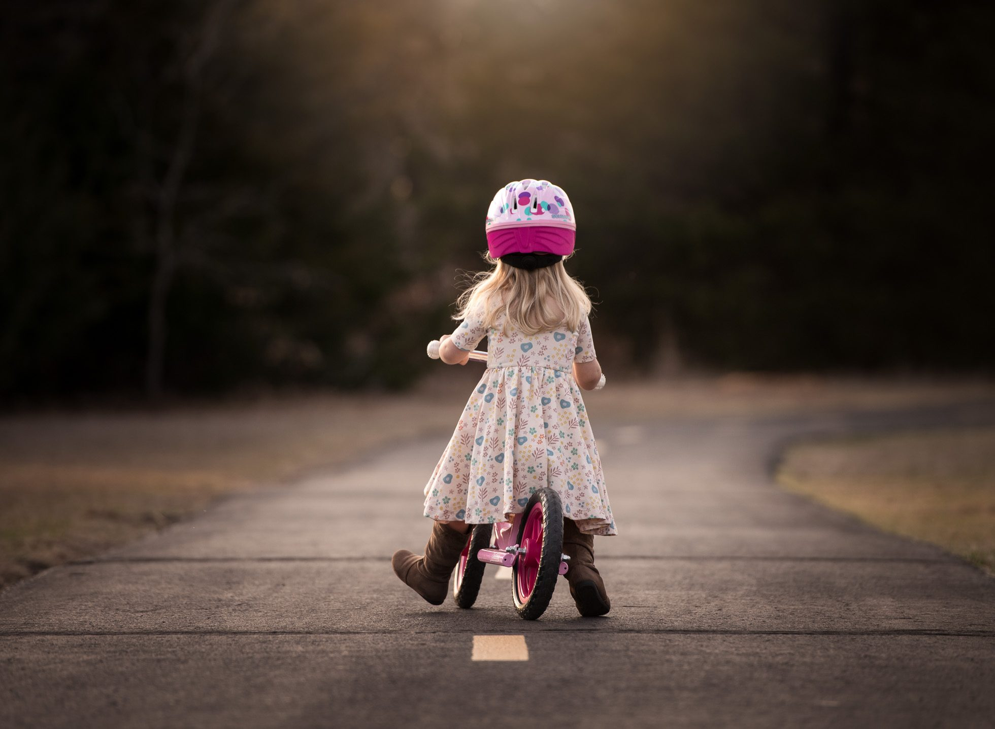 toddler girl riding balance bike down trail evening ride young girl on balance bike pink helmet edmond ok photographer oklahoma city natural light photographer kate luber photography