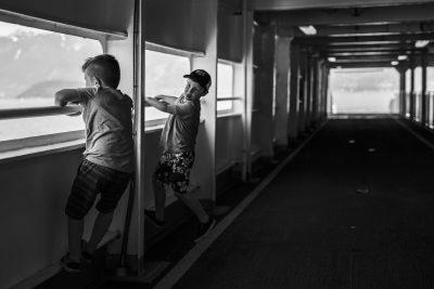 Black and white image of two little boys playing on the empty upper deck of a ferry boat.