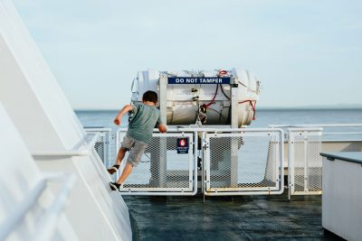 Boy running up the walls on a ferry boat.