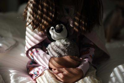Little girl holding her stuffed penguin tight