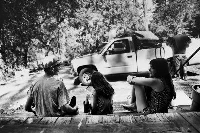 Three kids sitting on porch talking